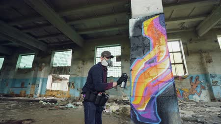 face painting : Low angle shot of young man is face mask painting graffiti on column inside empty industrial building using spray paint. Dirty damaged walls, windows and ceiling are visible.