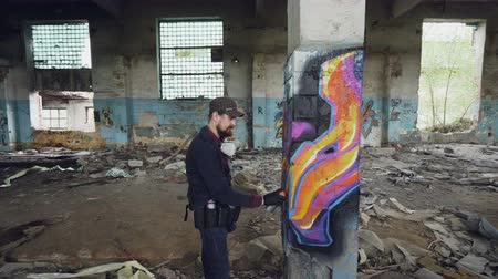vandalismo : Pan shot of damaged abandoned building with high columns inside and male graffiti artist drawing abstract images on pillar. Man has protective gloves and gas mask. Stock Footage