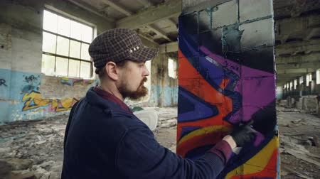 vandalismo : Close-up shot of handsome bearded man graffiti painter working inside adandoned building using earosol paint to create abstract image on pillar. Creativity and people concept.