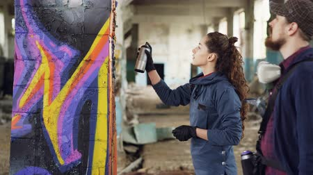 rehberlik : Cheerful young woman amateur graffiti artist is learning to work with spray paint from skilled bearded painter while decorating old column in empty warehouse.