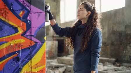 vandalismo : Serious young woman graffiti artist is painting on column in old warehouse using spray paint. Abandoned dirty building with litter on floor is in background.