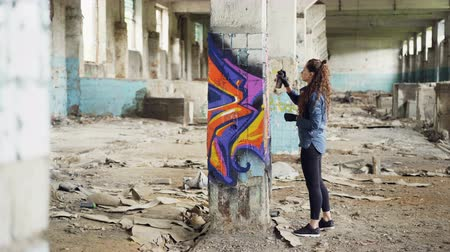vandalismo : Pretty girl graffiti artist is decorating old damaged column inside empty industrial building with abstract pictures. Modern painter is using aerosol spray paint. Stock Footage