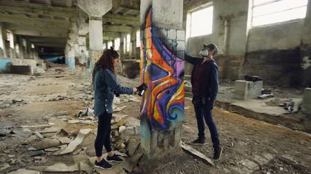 stopmotion : Time-lapse of graffiti artists are using aerosol paint to decorate abandoned industrial building with modern graffiti images. Creativity, street art and people concept. Stock Footage