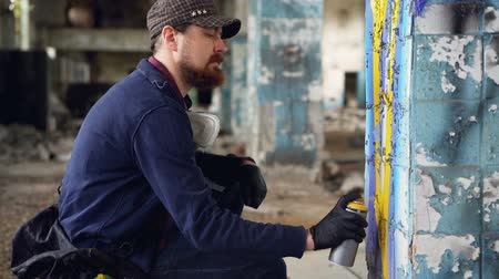 squatting : Serious adult man graffiti artist in leather gloves is painting on pillar inside damaged empty industrial building and squatting. Creativity and people concept.