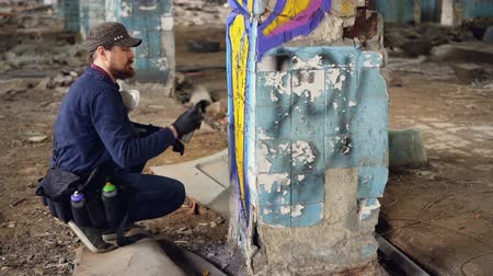 vandalismo : Modern graffiti painter is squatting near column in old abandoned building and painting graffiti with spray paint creating bright image. Creative people and art concept. Stock Footage