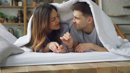 понимание : Loving couple girlfriend and boyfriend and lying in bed under blanket talking, laughing and kissing during happy weekend at home. Relationship and people concept,