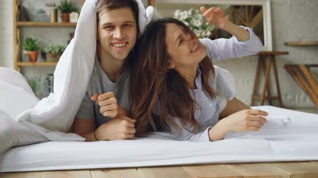 медовый месяц : Portrait of happy couple lying in bed under blanket then showing faces looking at camera laughing and smiling. Loving married people and happiness concept. Стоковые видеозаписи