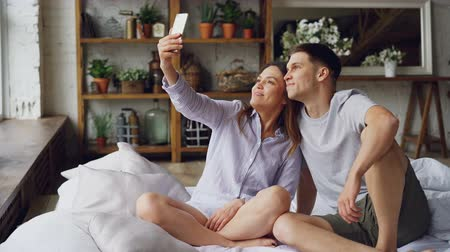 buta : Cheerful loving couple is taking selfie with smartphone looking at camera, posing and making funny faces while sitting together on bed at home. Technology and relationship concept.