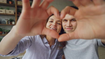 ingressou : Portrait of cheerful multiethnic couple making heart with their hands, looking at camera and smiling. Romantic relationship, married life and honeymoon concept.