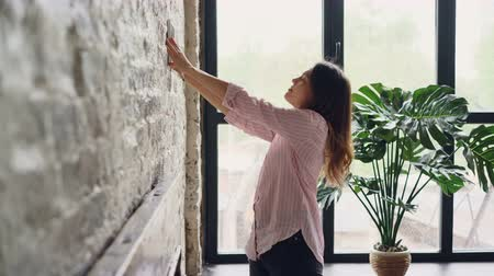 フレーム : Creative woman is decorating her loft style apartment choosing place on brick wall for beautiful picture and marking spot with pencil. Creativity and interior concept.