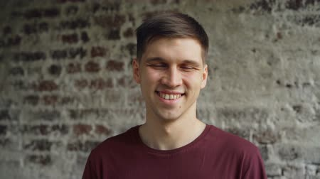 good looking guy : Slow motion portrait of young man in bright T-shirt looking at camera smiling and laughing with brick wall in background. Cheerful people and happiness concept.