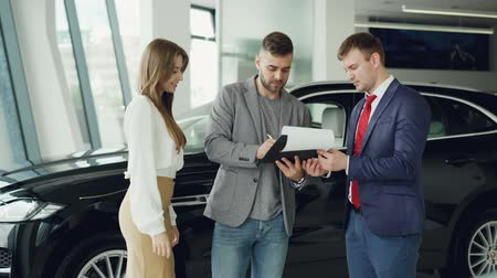 shaking hand : Handsome young guy is signing sale and purchase agreement in car dealership, getting key fob from salesman and giving it to his wife, she is smiling and kissing him. Stock Footage