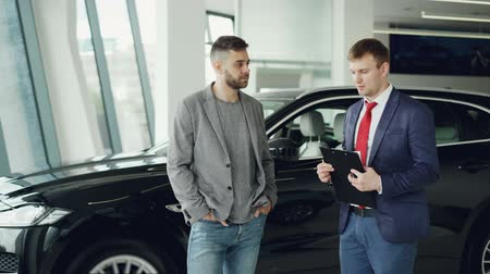 talk show : Handsome guy is talking to car dealership manager in motor show discussing new automobile model, dealer is holding documents and pen. Purchasing vehicle and people concept.