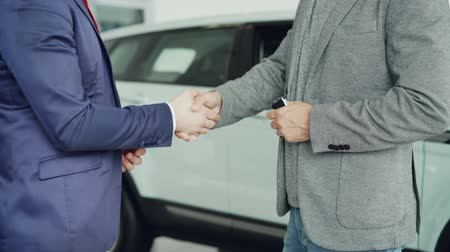 homem de negócios : Male worker of car showroom is giving car keys to buyer young man and shking hands with him standing beside luxurious new car. Selling and buying vehicles concept.