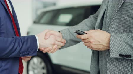 alku : Close up shot of male hands getting car keys after successful deal with sales manager and shaking hands. Buying and selling autos, businessmen and handshake concept.