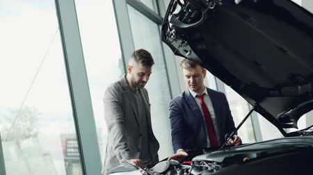 belirleme : Professional automobile salesman is demonstrating customer car engine under motor hood, men are looking at auto parts and talking. Buying and selling vehicles concept.