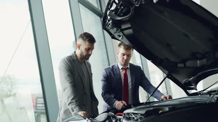 belirleme : Experienced car dealer is showing new customer engine under opened bonnet and telling him about quality and features of automobile model. Checking auto quality concept.