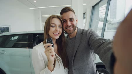 self promotion : Attractive young couple is taking selfie with car keys in modern motor showroom after buying new automobile. They are looking at camera, kissing and smiling.