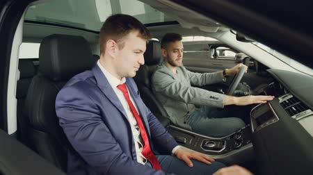 belirleme : Cheerful guy car buyer is talking to professional salesperson sitting inside expensive auto and touching instrument board and steering wheel. Conversation and test drive concept.