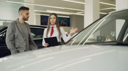 satmak : Attractive female car dealer is talking to interested customer about new automobile model and holding documents while standing together near beautiful car. Stok Video