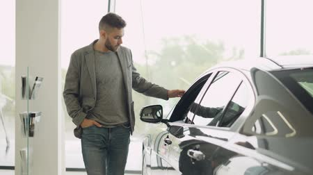 мысль : Interested customer is inspecting beautiful automobile in motor showroom, looking at car and touching it. Focus on shiny new auto, mans reflection is visible.