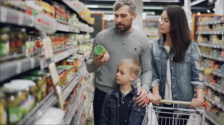 konserve : Married couple with cute little son are shopping for food, they are taking glass can from shelf and checking ingredients and expiry date and talking.