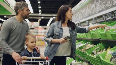 troli : Handsome bearded guy, his attractive wife and cute child are choosing vegetables in trays in supermarket, talking, laughing and putting products in trolley. Stock mozgókép