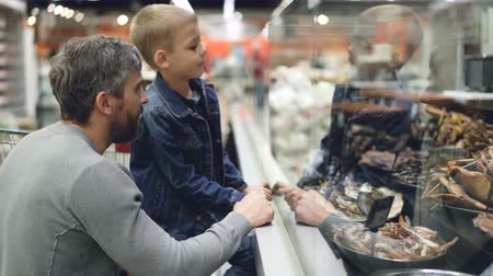 finom : Father and little son are looking at food through glass in supermarket, man is pointing at products, laughing and talking to his son, curious boy is smiling.