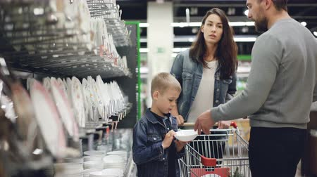 finom : Smiling family is buying bowls and plates in kitchenware department in hypermarket, they are taking dishes from shelf and putting in shopping trolley. Stock mozgókép