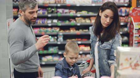 troli : Young family mother, father and child and choosing sweets in food store, taking products and looking at them then putting in trolley. Shelves with tasty food are visible. Stock mozgókép