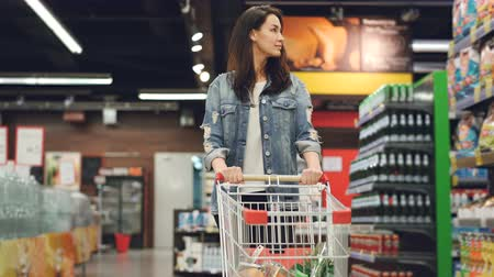 troli : Pretty lady in casual clothes is walking in grocery store steering shopping trolley with food inside it and looking around at shelves with products. Women and shops concept. Stock mozgókép