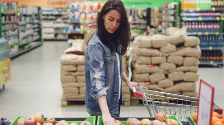 reparto : Attractive girl happy customer is choosing fruit in supermarket buying bananas, apples and oranges and putting them in shopping cart. Healthy lifestyle and shops concept. Filmati Stock