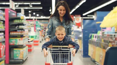 troli : Joyful loving mother is having fun in supermarket with her cute little son, she is running with shopping cart with small boy standing on it, people are laughing. Stock mozgókép