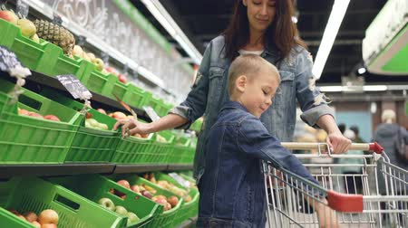 two rows : Cute blond boy is shopping with his mother buying fruit, he is taking apple from plastic box and putting it in trolley, his mom is smiling and talking to her son.
