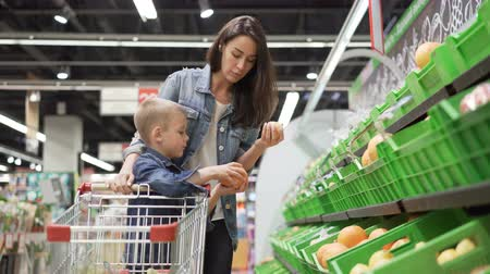 two rows : Young woman and her son are choosing fruit in store, they are taking fruit from plastic boxes and smelling them then putting in trolley. Family, shop and healthy lifestyle concept.