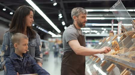 fartuch : Mother and child are buying baked roll in supermarket, salesman in apron is putting food in plastic bag and giving it to customers. Selling and purchasing food concept.