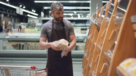 lojas : Male employee of large supermarket is taking fresh bread from shopping cart and putting it on shelves in bakery department. Selling food and people concept.