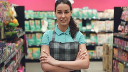 vendedora : Portrait of attractive young saleswoman in apron standing in supermarket with her hands crossed, looking at camera and smiling. Trade business and people concept.