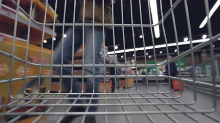 aisles : Shopping trolley is moving quickly along aisles in supermarket, shelves with food, drinks and goods are visible through cart grille. Shopping and customers concept. Stock Footage