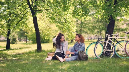 recreational park : Pretty Caucasian girl is talking to her African American friend and laughing during break after riding bicycles, young women are sitting on lawn in park and chatting.