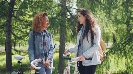 sharing : Two pretty female bicyclers with backpacks are talking standing in the park holding bikes. Pan shot of beautiful city park with many trees and green lawns.