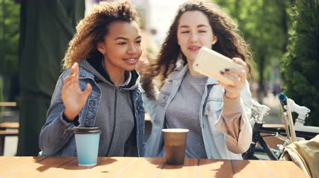 dinlenmek : Female friends are taking selfie with smartphone sitting in street cafe at table then watching photos and laughing touching screen. Friendship and photographs concept. Stok Video