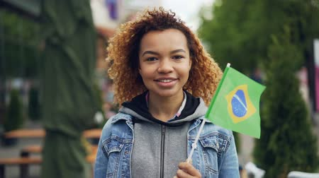 brazil : Slowmotion portrait of cheerful African American girl looking at camera and holding Brazilian flag standing in nice park in modern city. Tourism and people concept.