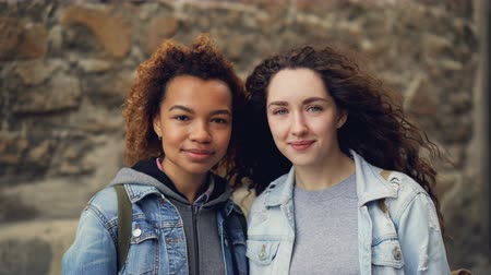 ветреный : Close-up portrait of two pretty young women friends standing together near stone wall, smiling and looking at camera. Mixed-race friendship and people concept.