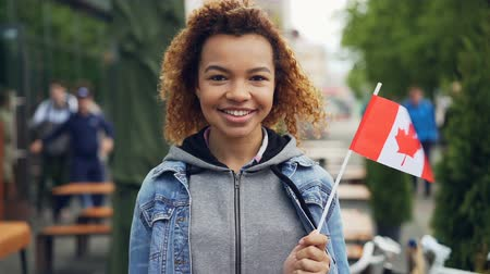 kanada : Slowmotion portrait of smiling African American girl traveller holding Canadian flag and looking at camera outdoors. Happy tourist and visiting foreign coutries concept. Stok Video
