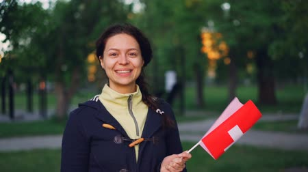 happiness symbol : Slow motion portrait of merry Swiss girl waving flag of Switzerland, smiling and looking at camera. Beautiful park with high trees and green lawns is in background. Stock Footage
