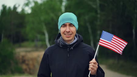 gururlu : Slow motion portrait of handsome guy American citizen holding flag of the United States, smiling and looking at camera. Citizenship, people and countries concept. Stok Video