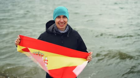 spaniard : Slow motion portrait of happy Spanish sports fan holding national flag of Spain standing on sea coast and smiling. Patriotism, active lifestyle and people concept.