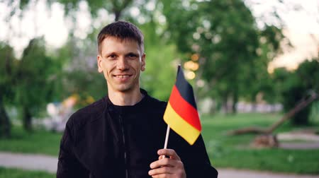foreigner : Slow motion portrait of cheerful German fan waving official flag and looking at camera while standing in great modern park with beautiful trees and lawns.
