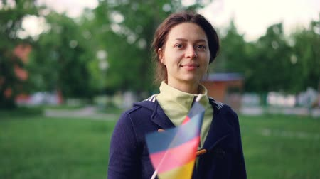 foreigner : Slow motion portrait of cheerful young woman waving official German flag and looking at camera while standing in nice green park with beautiful trees and lawns.